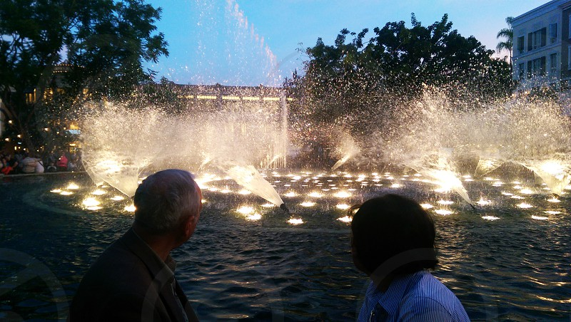 man and a woman sitting watching the waterfountain photo