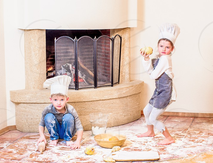 Two siblings - boy and girl - in chef's hats near the fireplace sitting on the kitchen floor soiled with flour playing with food making mess and having fun. photo