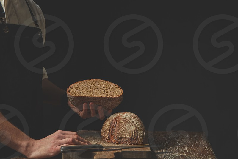 Baker holding a half of freshly baked bread in a hand on a dark background Tonned photo photo