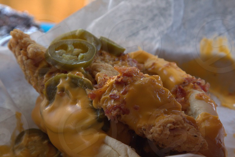 The Bird Dog -- deep fried chicken strips topped with bacon jalapenos and nacho cheese sauce in a hot dog bun.  state fair food photo