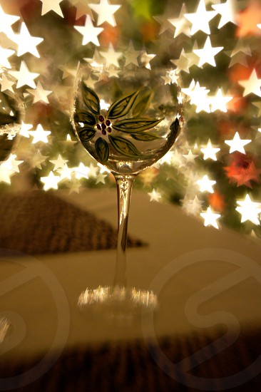 Painted holiday wine glass in front of a Christmas tree with star shaped bokeh photo