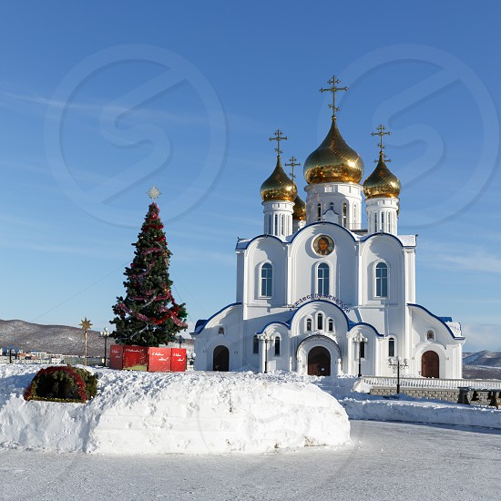 PETROPAVLOVSK CITY KAMCHATKA RUSSIA - JAN 6 2018: Building of Holy Trinity Orthodox Cathedral of Petropavlovsk Kamchatka Diocese of Russian Orthodox Church and Christmas tree in front of building photo