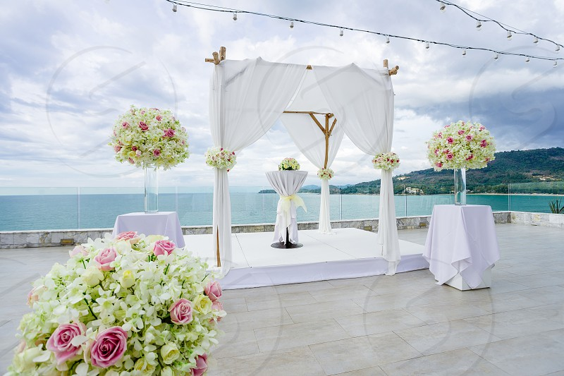 Wedding venue setup for ceremony with the panoramic ocean and island view in background. Wedding arch altar decoration with roses flowers floral photo