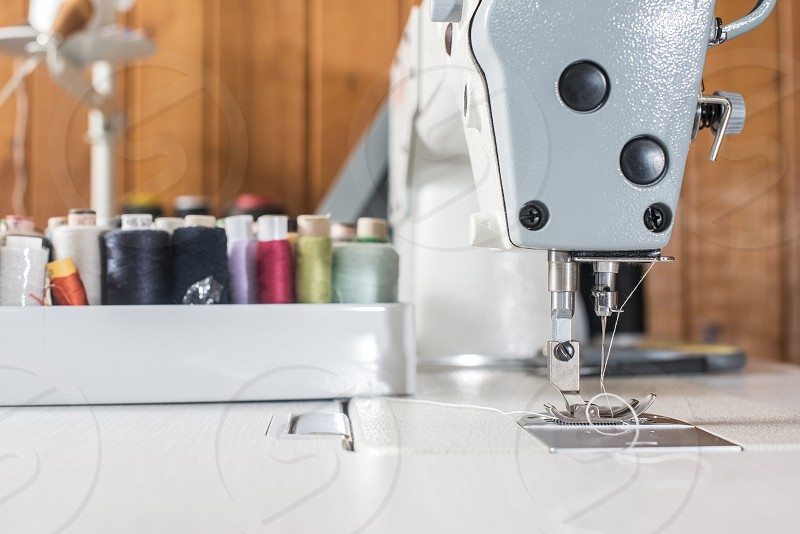 Woman sewing on a sewing machine. Close up photo