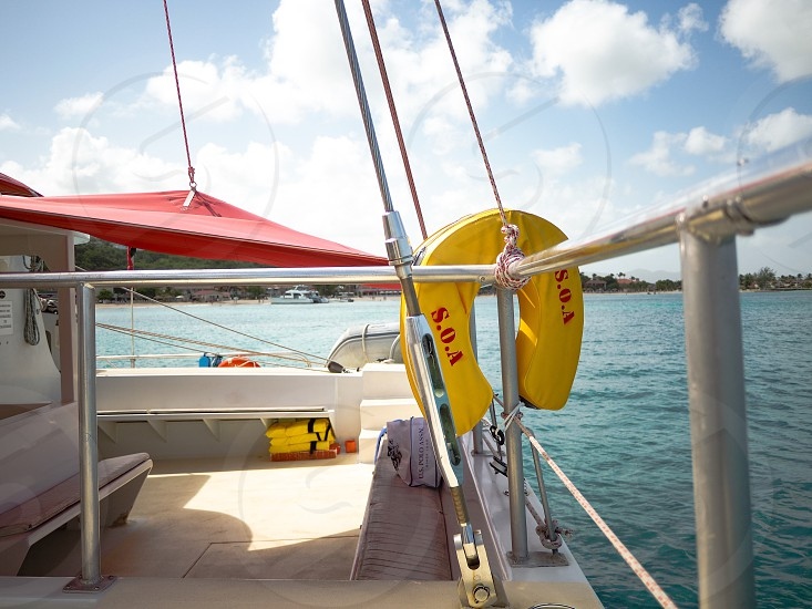 yellow and red s.o.a. floater hanged on stainless steel bars of yacht photo