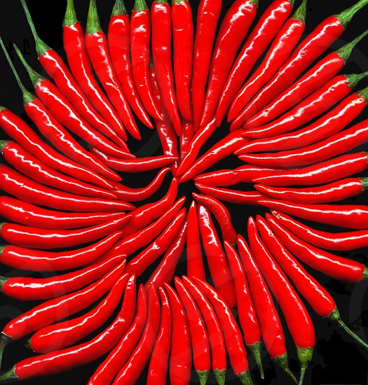bounch of red cili peppers on circular composition black background photo