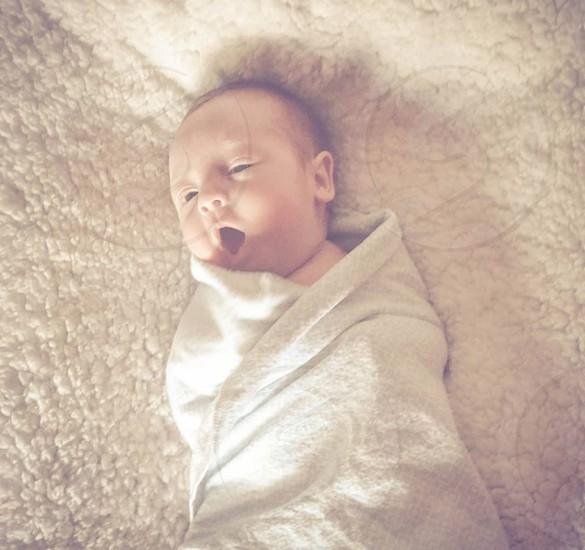 baby in white blanket photo
