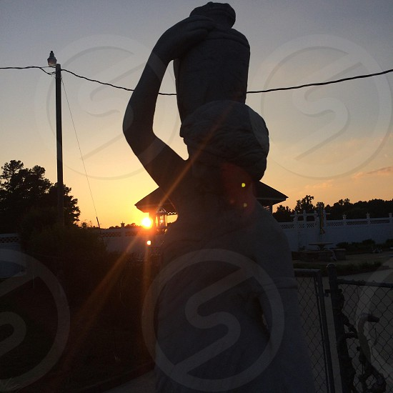 The sunset behind a statue of a woman holding a pot photo