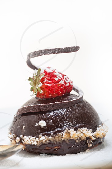 fresh chocolate strawberry mousse over white with silver spoon photo