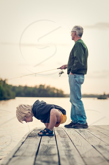 child children fishing boy family people youth kid grandpa generations wonder looking sweatshirt lake water dock blue navy gray yellow trees fish pole rod blonde hair sandals reel sunset dusk evening forest woods vacation relax peaceful serenity wilderness outdoors outside photo