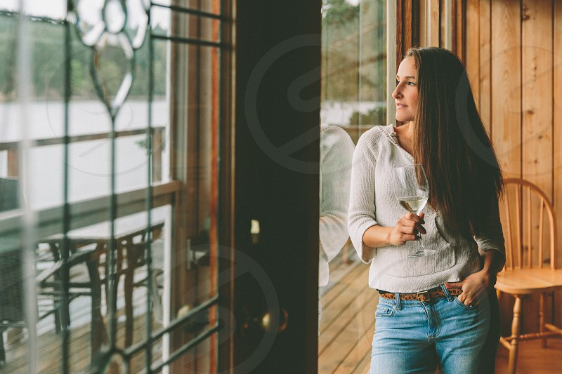 A young woman looking out the window thoughtfully while drinking wine.  photo