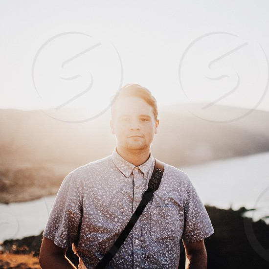 man in gray white floral button up shirt carrying sling bag during sunset photo