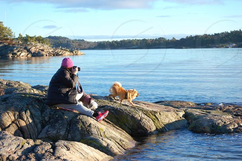 person wearing pink knit cap using camera next to lake photo