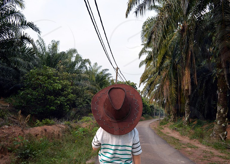 boy little wearing cowboy hat on country road photo