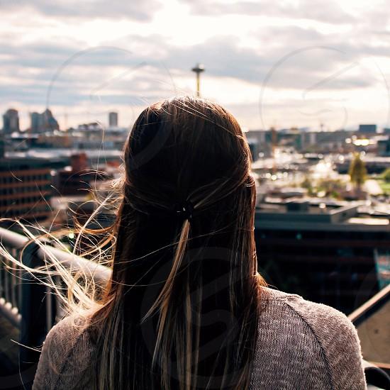 woman in grey shirt facing the buildings photo