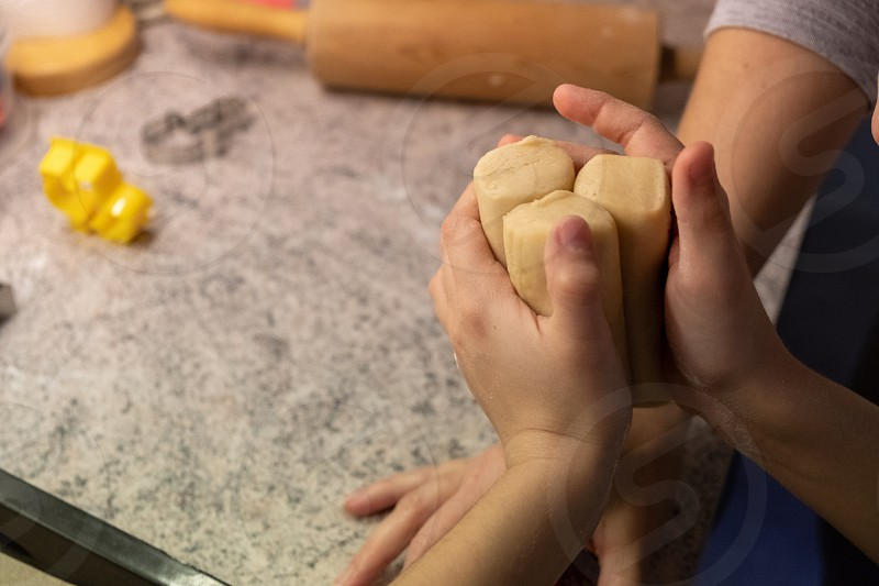 Child shaping and cutting baking cookies for christmas photo