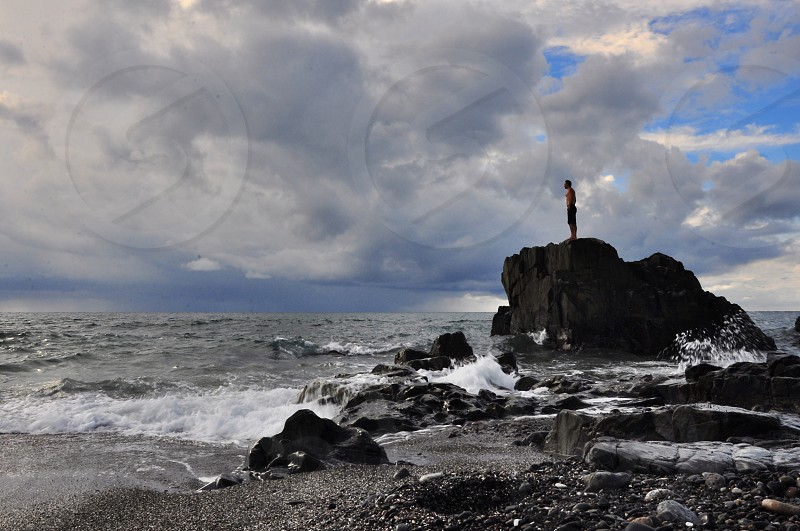man standing on rock on shore photo