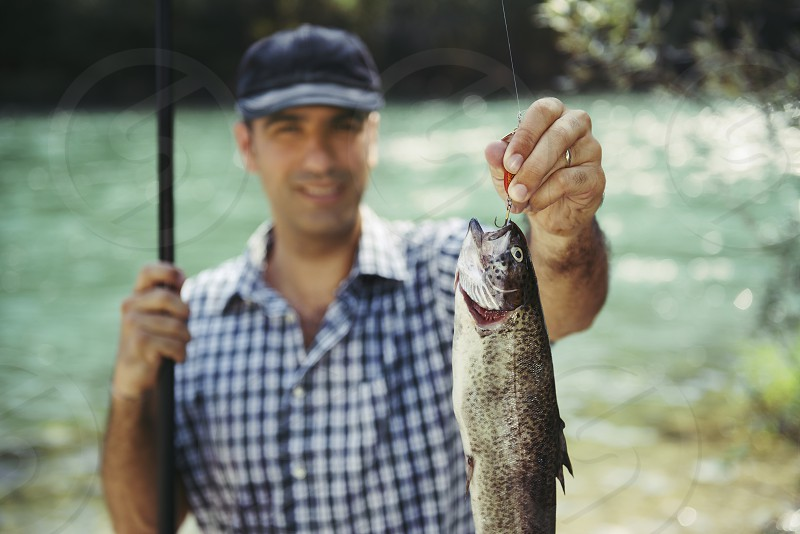 fish; fisher; fisherman; fishing; trout; showing; sport; 40s; active; activity; adult; angler; bait; cap; catch; equipment; fishing rod; focus on foreground; fun; happy; hat; hobbies; hobby; holiday; hook; lake; leisure; lifestyle; looking; camera; lure; male; man; nature; one; outdoor; people; person; pride; proud; relax; river; rod; smile; smiling; sports; stream; summer; vacation; water photo