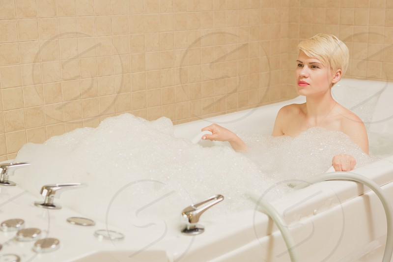 woman in red lipstick on white ceramic bathtub photo