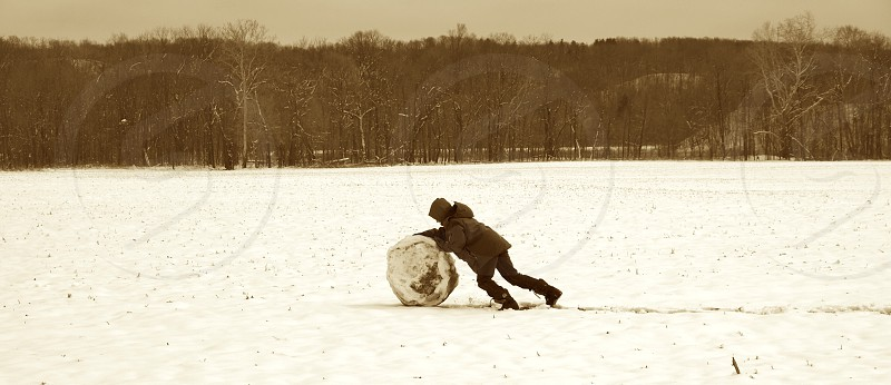 Winter. Child rolling large snowball. photo