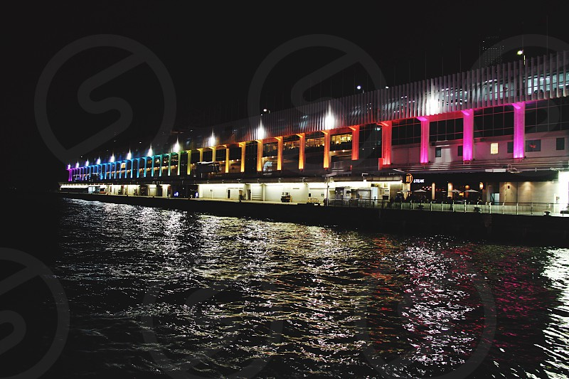 lighted architectural structure near body of water at night time photo