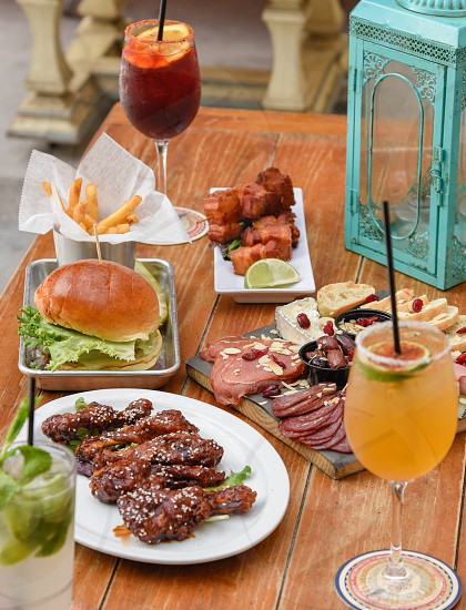 french fries beside burger and cooked chicken beside orange and line citrus drink and ham on wooden surface photo