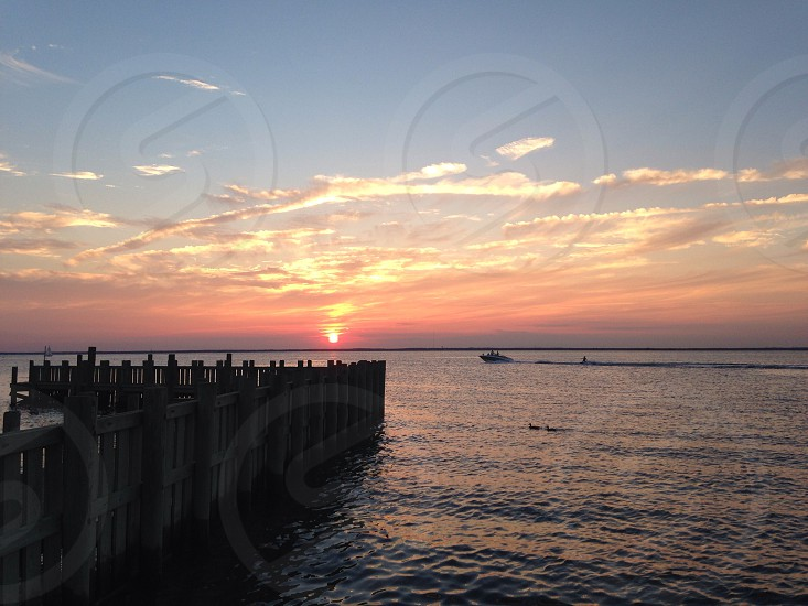 brown wooden fence on sea with sunset background photo