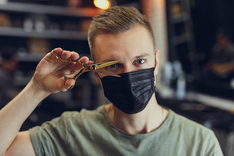 Hairdresser wear mask and hold scissors near his face. - Image photo