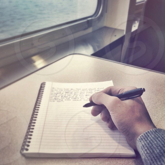 person writing on notebook photo