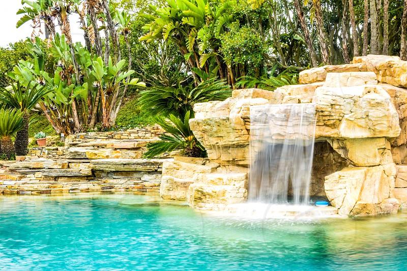 artificial waterfalls on swimming pool during daytime photo