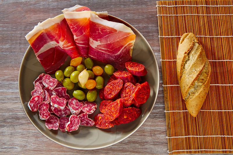 Tapas of Spain with ham bread olives sausage and chorizo on wooden background photo