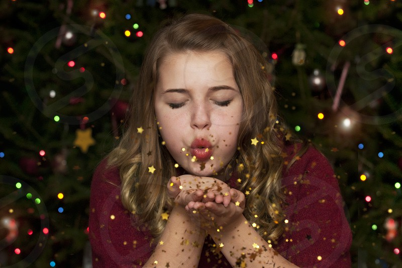 Teenage girl wearing a red sweater blowing gold stars in front of a decorated tree at Christmas. photo