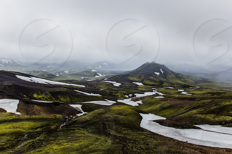 Icelandic landscape during hike from Landmannalaugar to Þórsmörk. Hills with bright green moss and contrasty white snow. photo