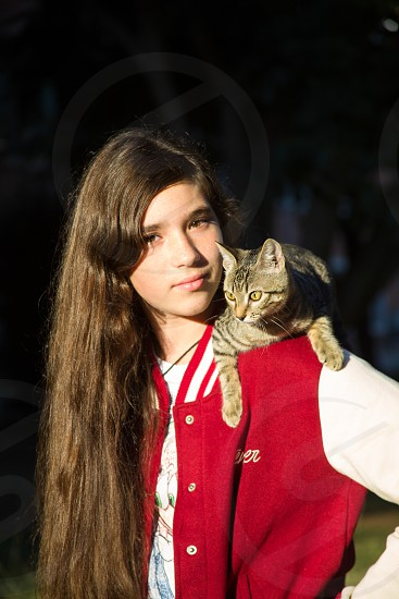 A girl with a cat on her shoulder photo