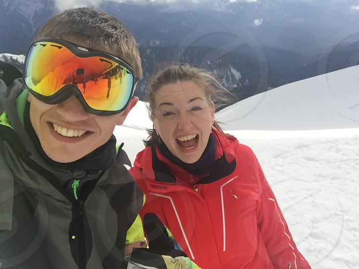 man wearing black jacket and woman wearing red jacket on snowfield photo