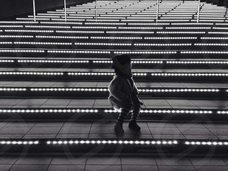 toddler sitting on concrete stairs with lights on in grayscale photography photo