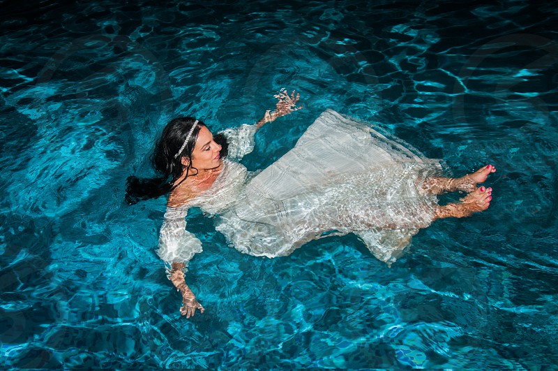 woman in white dress in body of water during daytime photo