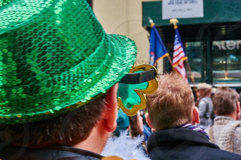 man in green sequin bucket hat standing amidst crowd photo