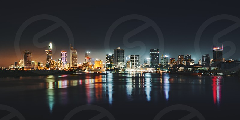 Urban night skyline panoramic view of Ho Chi Minh city. Front view on colored skyscrapers in downtown from the river photo
