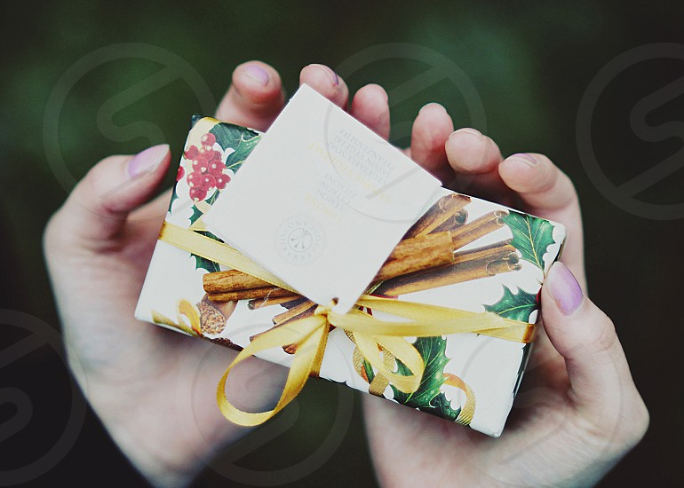 hands gift present wrapped gold cinnamon christmas holly berries holding for you photo