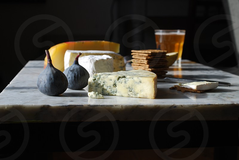 Selection of cheeses fruit and beer on marble surface. photo