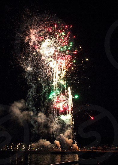 Red green and white fireworks in succession over lake with lake lights photo