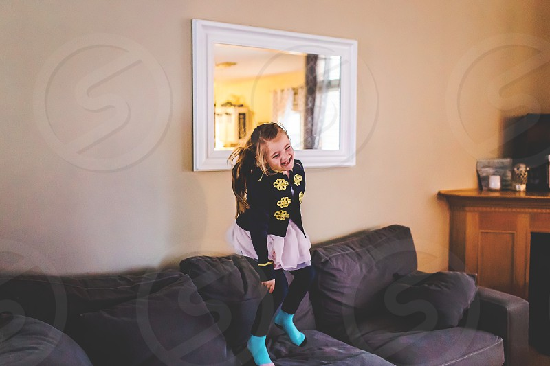 young girl jumping on couch in living room photo