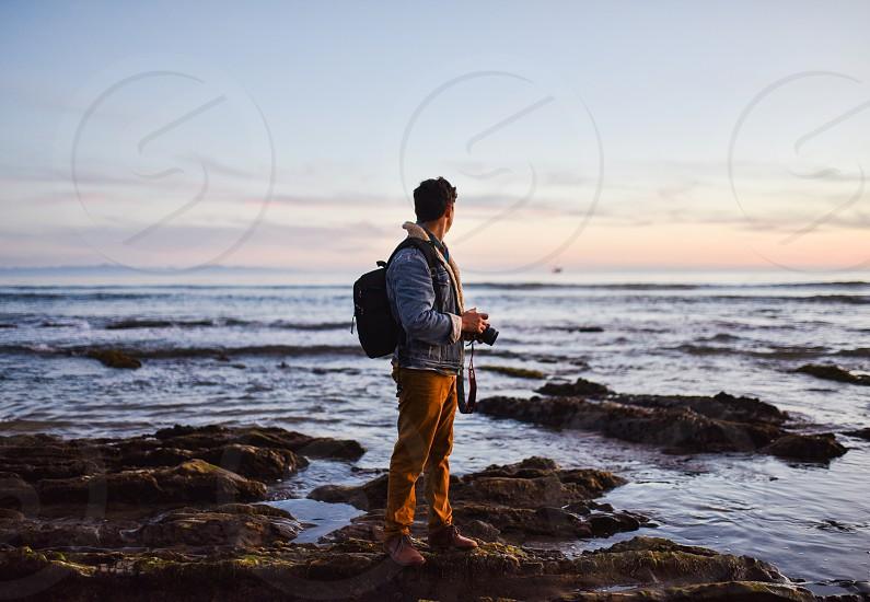 man camera photographer sunset beach ocean photo