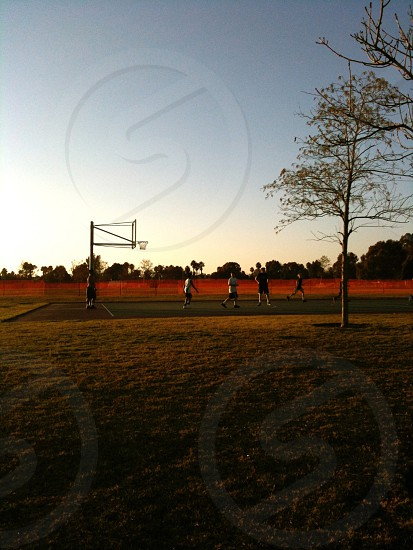 group of boys playing basketball under blue sky photo
