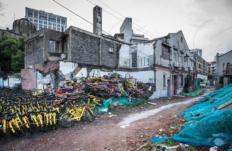 The  backside of the shared bike economy in China. Huge places with bicycles to be rolled out in the city. Run down houses garbage just a street apart form the luxury modern city photo