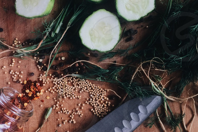 sliced cucumbers green leaves and brown and orange seeds photo