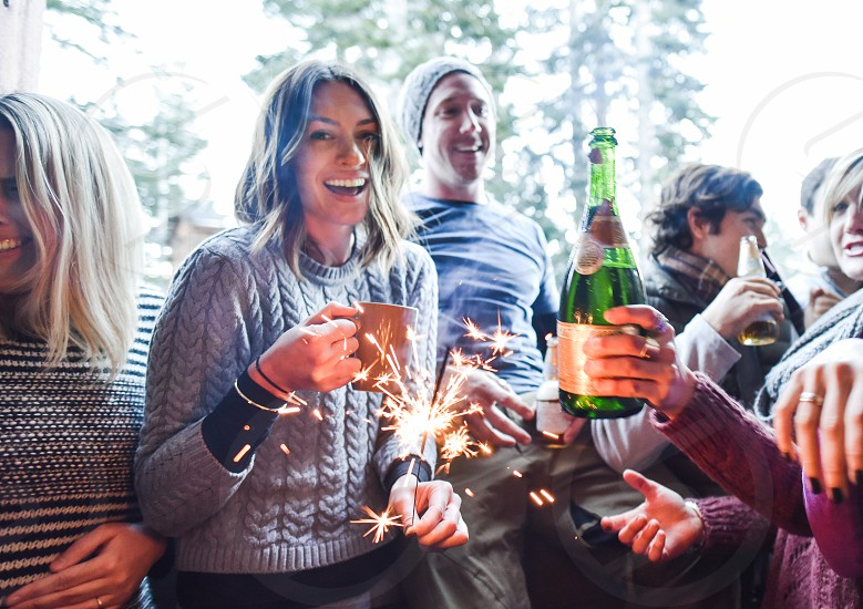 woman in gray knit sweater holding sparklers between people near green trees during daytime photo