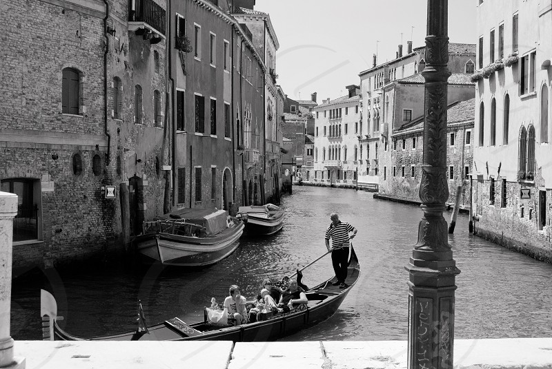 people riding canoe in venice canal in grayscale photo