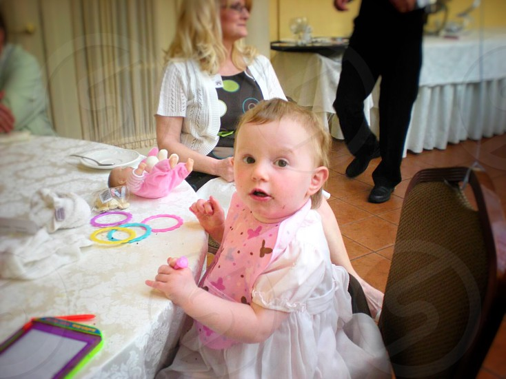 baby in white dress with pink bib sitting near white table with toys photo